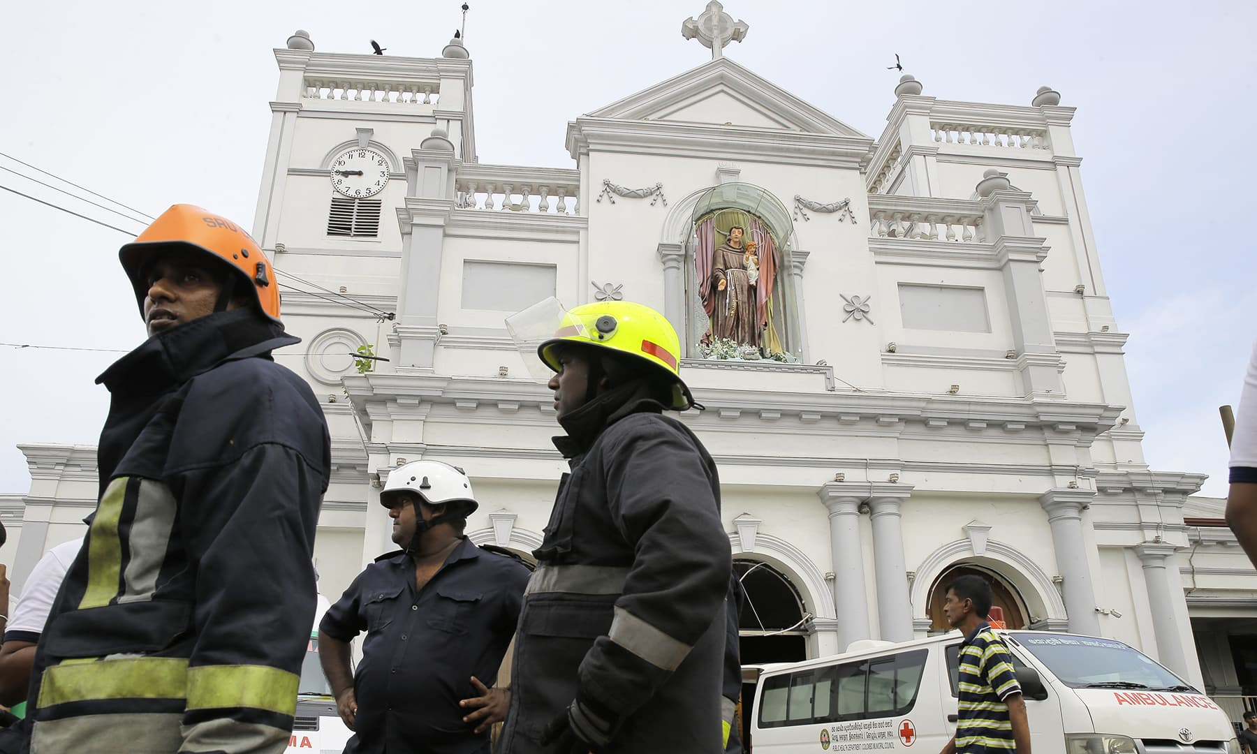 Sri Lankan firefighters stand in the area around St Anthony's Shrine after a blast in Colombo. — AP