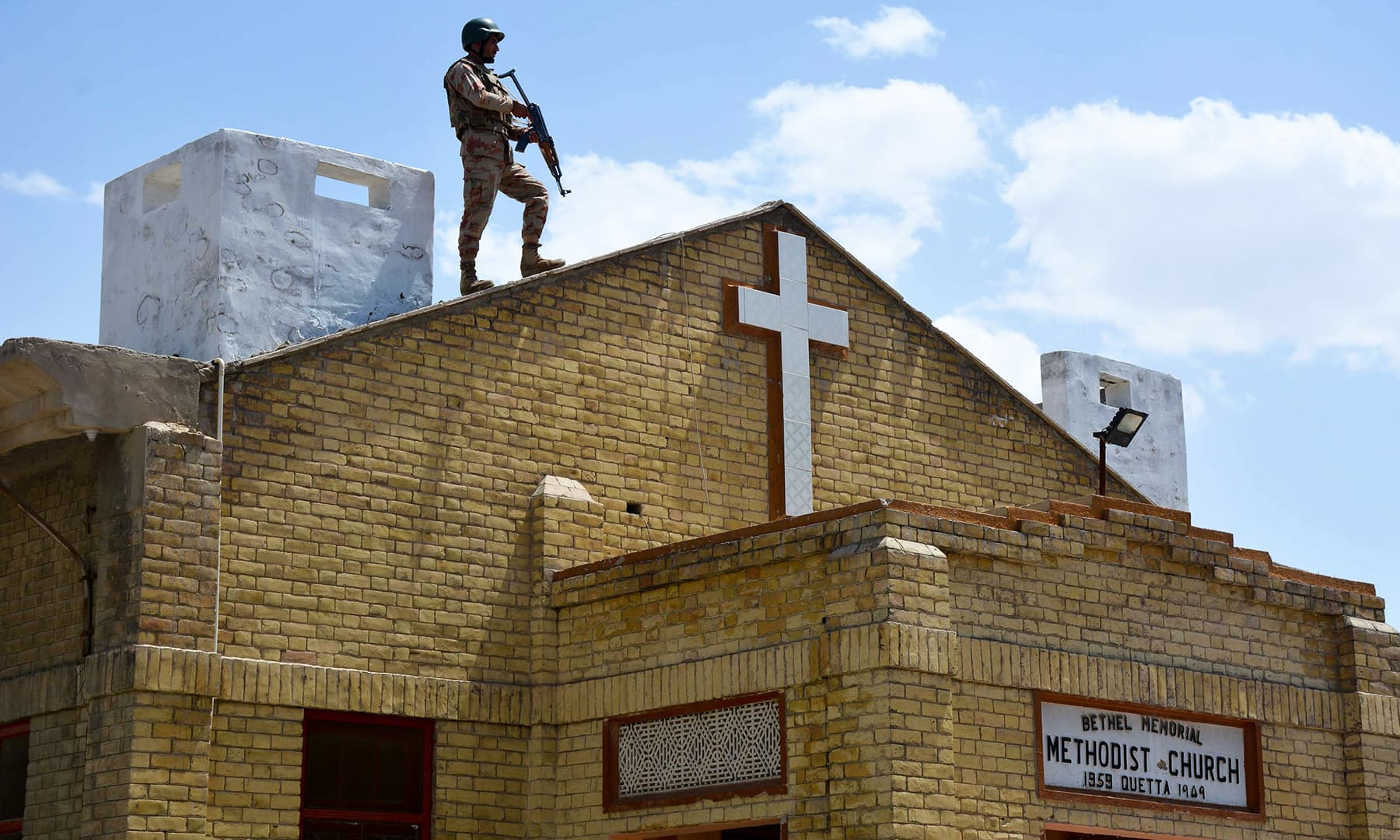 A soldier stands guard on the roof of a Methodist Church during the Easter service in Quetta. — AFP