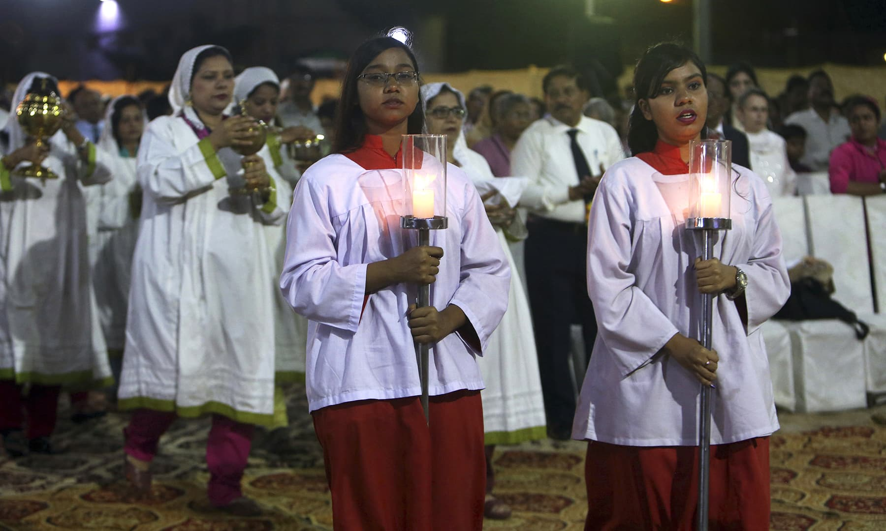 Christians carry candles during an early morning Easter mass at St Patrick's Church in Karachi. — AP