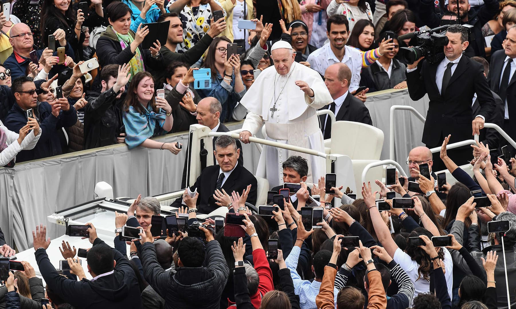 Pope Francis waves to worshipers from the popemobila car as he leaves at the end of the Easter Sunday mass. — AFP