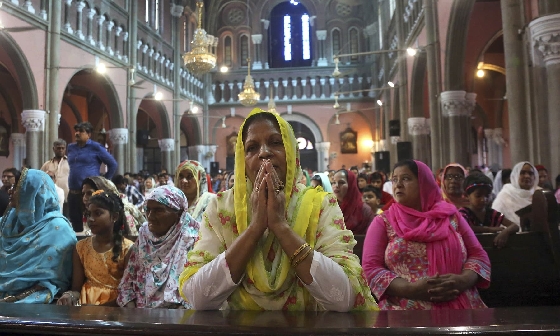 A woman prays during Easter mass at Catholic Sacred Heart Cathedral in Lahore. — AP