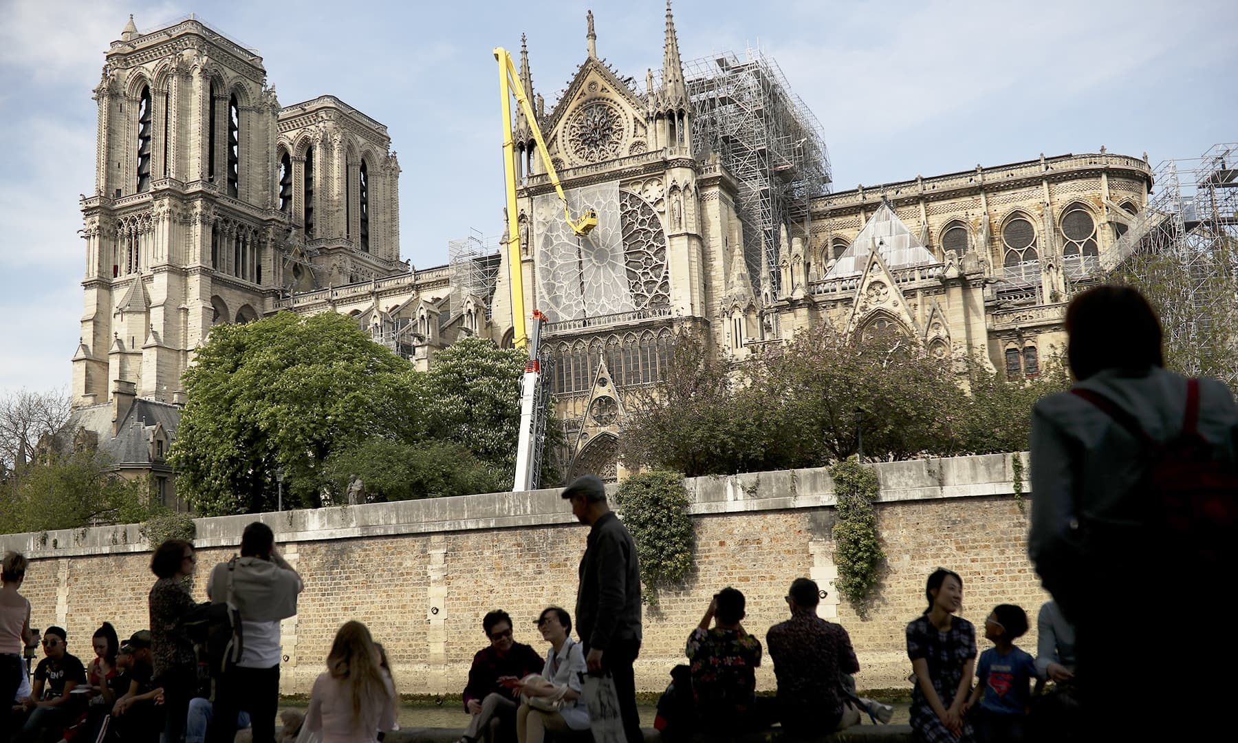 Workers, top, fix a net to cover one of the iconic stained glass windows of the Notre Dame Cathedral in Paris. — AP