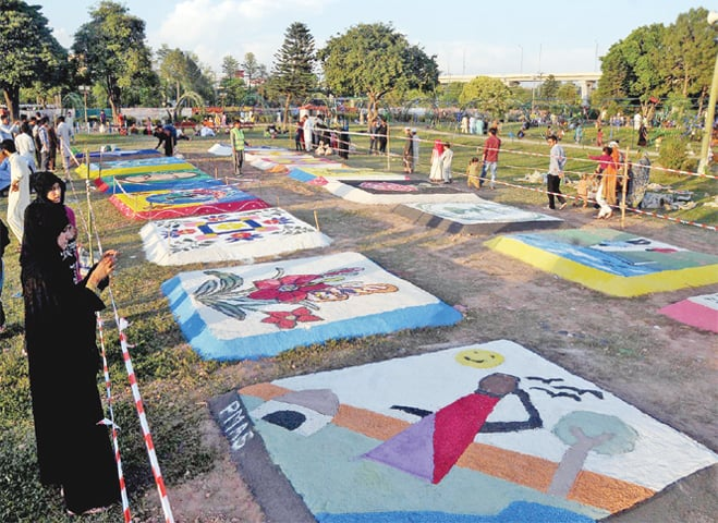 Visitors look at art work on crushed stones displayed at the spring festival at Nawaz Sharif Park in Rawalpindi on Sunday. — White Star