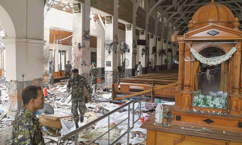 SECURITY men walk past bodies covered with blankets amid blast debris at a church in Colombo.—AFP