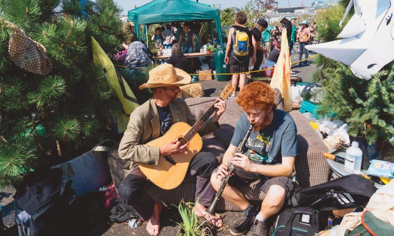 Climate change activists play music at Waterloo Bridge on Sunday.—AFP