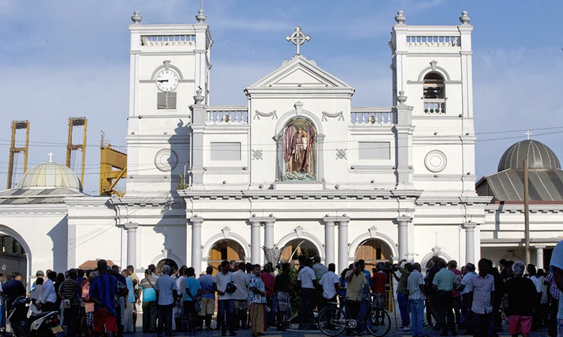 People gather outside St Anthony's Shrine a day after a blast targeted it. ─ AP