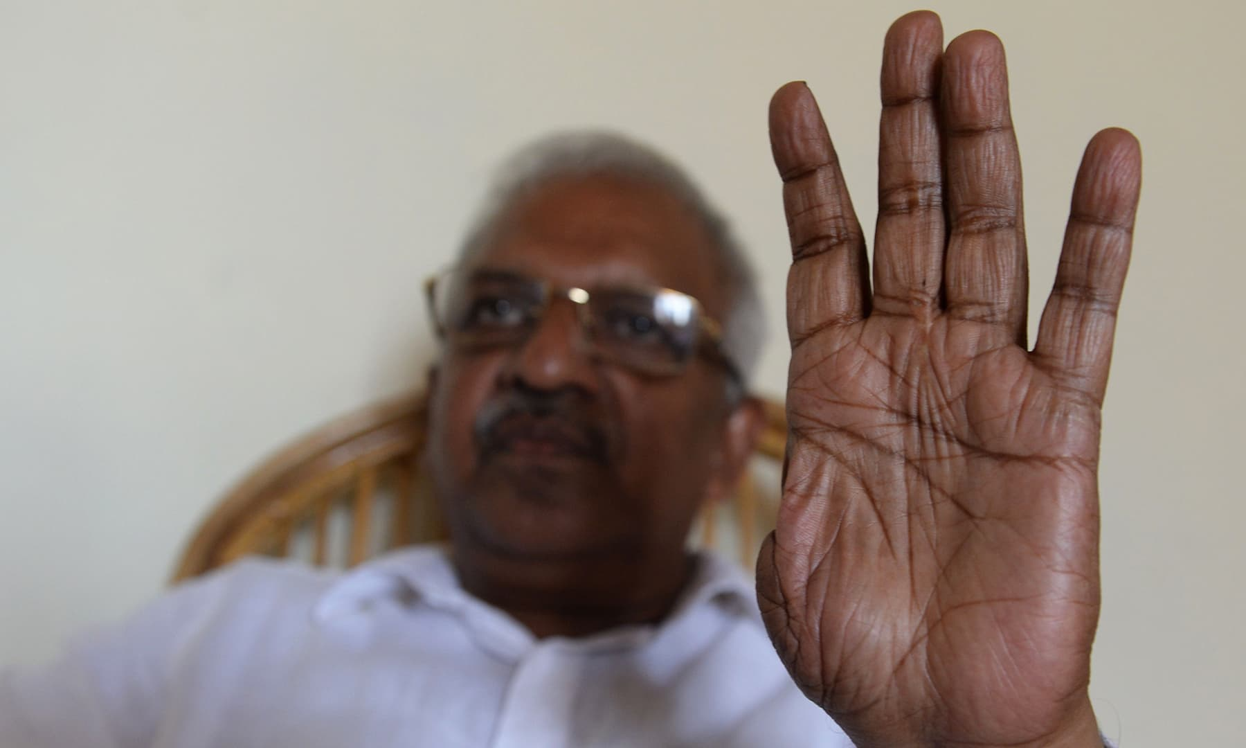 In this photo taken on April 19, P. Jayarajan, a Communist Party of India (Marxist) electoral candidate, holds up his thumbless hand during an interview with *AFP* at Vadakara in the southern Indian state of Kerala. — AFP