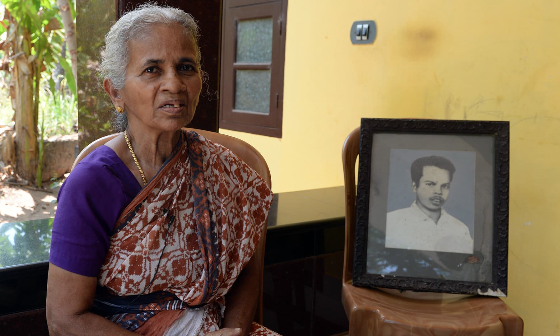B.N. Leela, the widow of Vadekkal Ramakrishnan, who was one of the first Rashtriya Swayamsevak Sangh (RSS) members killed in political violence, sits beside the portrait of her late husband during an interview with AFP at Thalaserry. — AFP