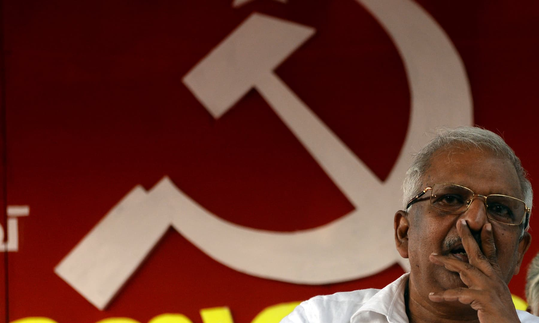 P. Jayarajan, a Communist Party of India (Marxist) electoral candidate and who was a target of political violence in 1999, holds up his thumbless hand during an interview. — AFP