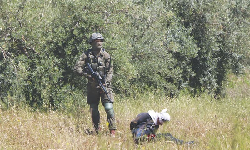In this April 18 photo, an Israeli soldier stands over handcuffed and blindfolded Osama Hajahjeh after he was shot near a village in West Bank. — AP