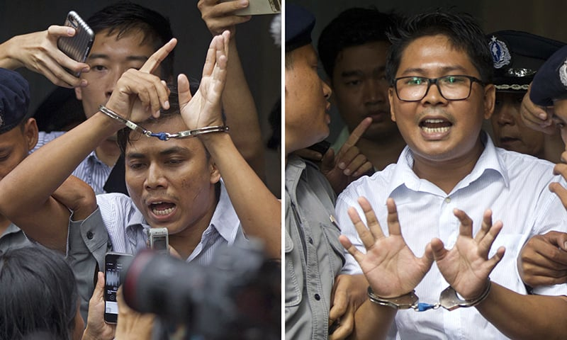 In this Sept. 3, 2018, combination file photo, Reuters journalists Kyaw Soe Oo, left, and Wa Lone, are handcuffed as they are escorted by police out of a court in Yangon, Myanmar. ─ AP/File