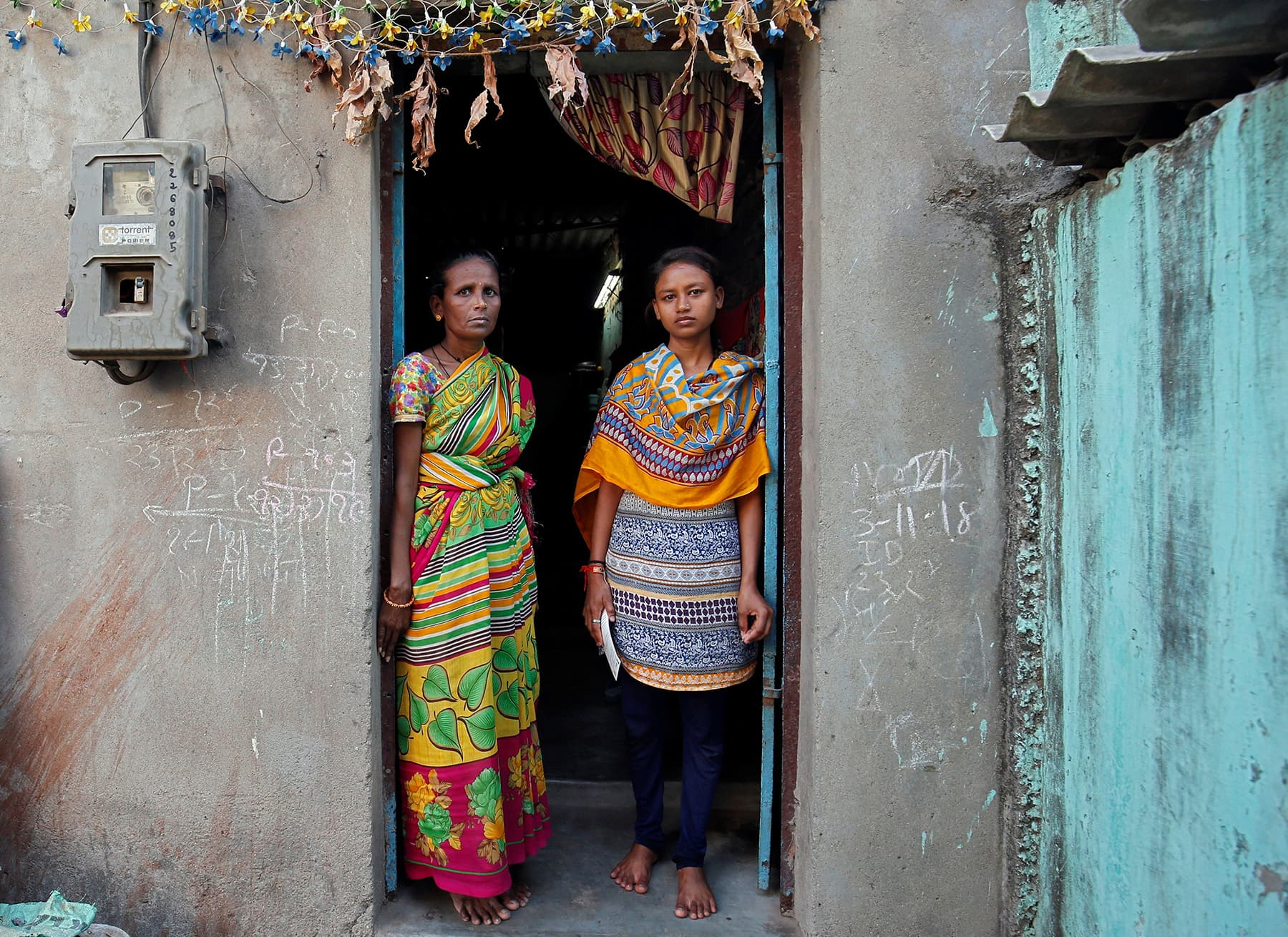 Pooja Jadhav, 18, poses with her mother as they stand at the entrance of their house in Ahmedabad, April 12. — Reuters