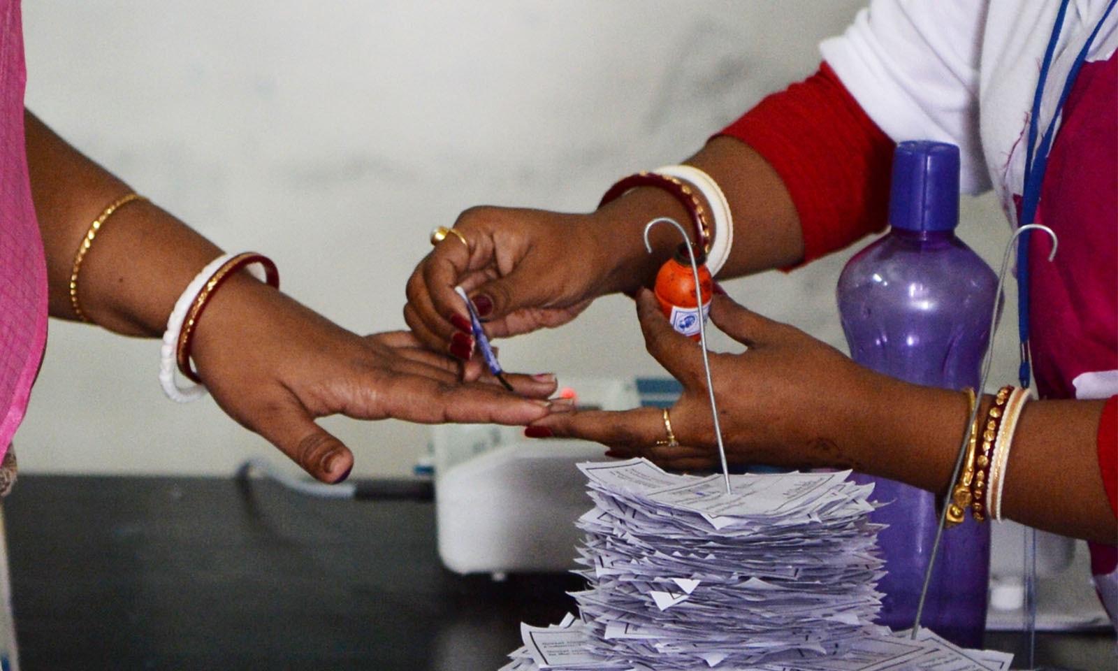 مالڈا کے پولنگ اسٹیشن پر انتخابی افسرووٹر کی انگلی پر انمٹ سیاہی لگا رہی ہیں—فوٹو: اے ایف پی
