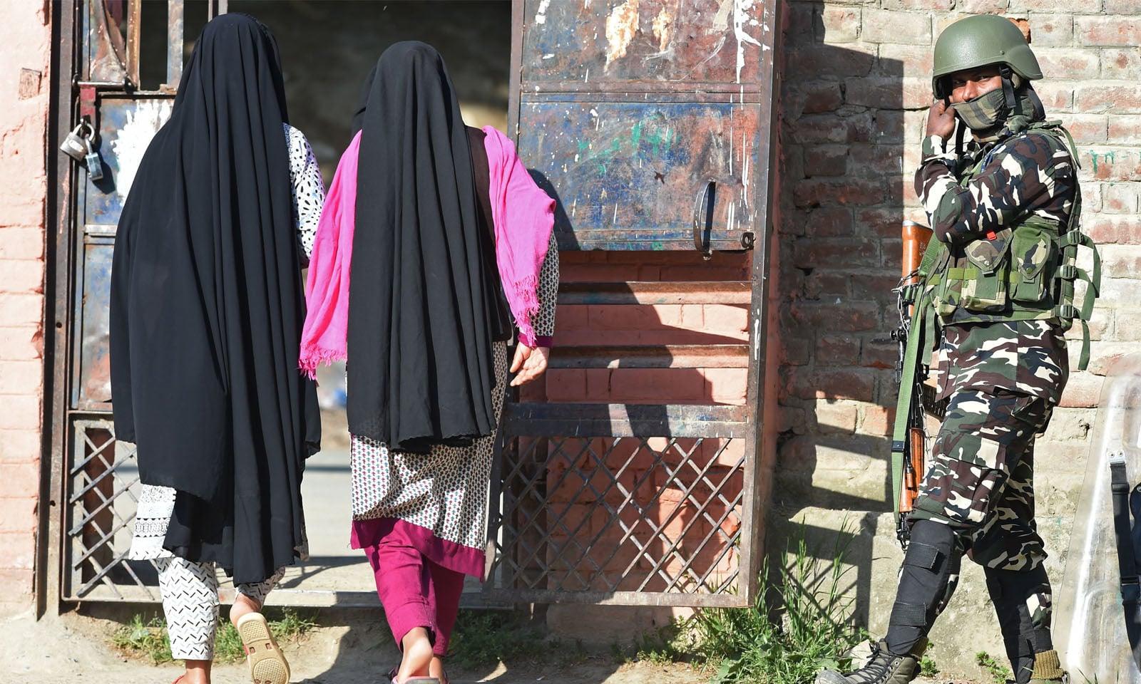 مقبوضہ کشمیر میں خواتین الیکشن آفس میں ووٹ ڈالنے کے لیے داخل ہو رہی ہیں—فوٹو/ اے پی