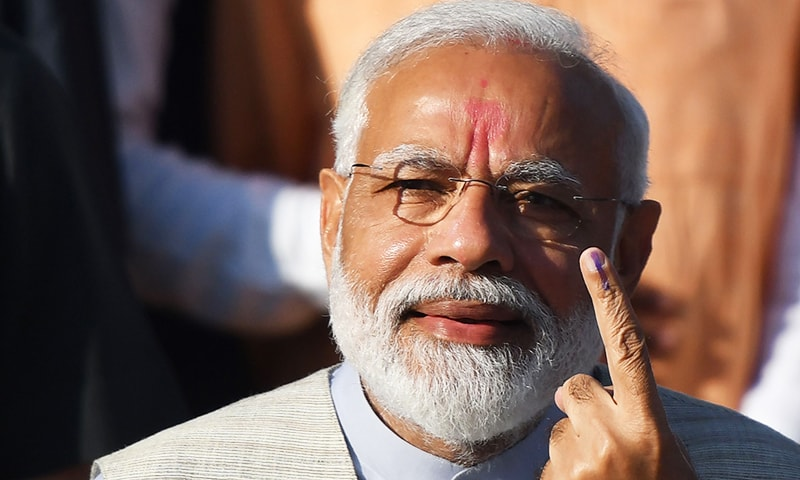 Indian Prime Minister Narendra Modi displays his ink-marked finger after casting his vote during the third phase of general elections at a polling station in Ahmedabad on April 23. — AFP