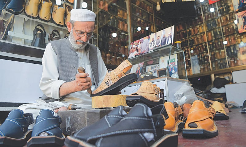 Chacha Noor Din, the owner of a string of shoe stores, makes a pair of sandals at one of his shops in Peshawar.—AFP