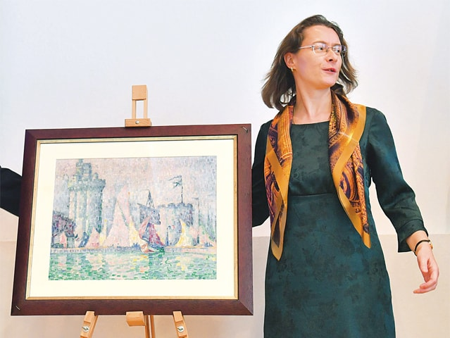 Kiev: The French ambassador to Ukraine, Isabelle Dumont, looks at a painting, Port de la Rochelle (1915) by French artist Paul Signac, during its presentation at the Ukrainian ministry of internal affairs on Tuesday.—AFP