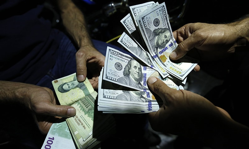 In this file photo taken on August 8, 2018, a man exchanges Iranian Rials against US Dollars at an exchange shop in the Iranian capital Tehran. — AFP/File