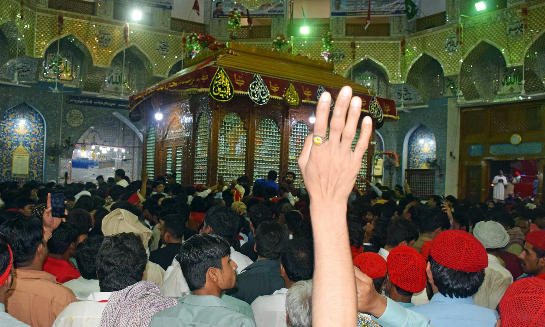An inside view of Qalandar's shrine. Visitors have filled the space completely.