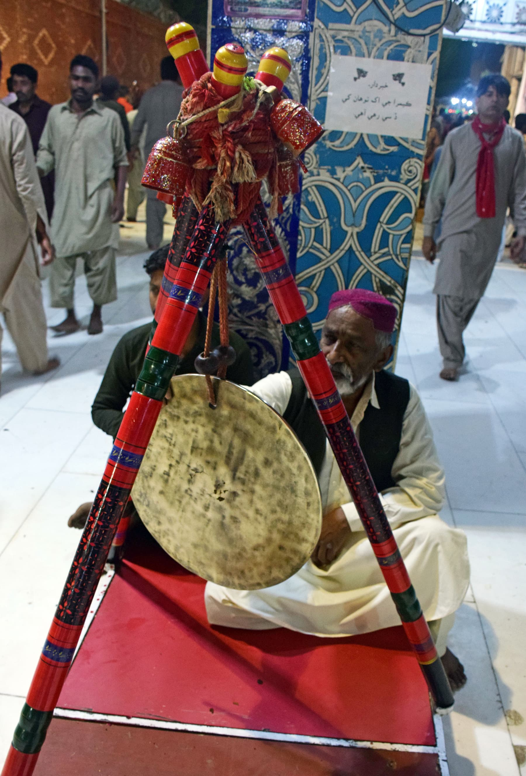 An elderly devotee sits in the shrine's courtyard to bang on a gong as a signal.