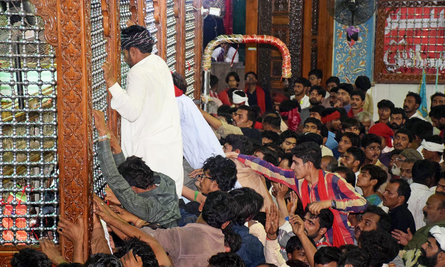 Devotees struggle to touch the brown wooden frame built around the grave of Qalandar and called *zari* in the spiritual order.