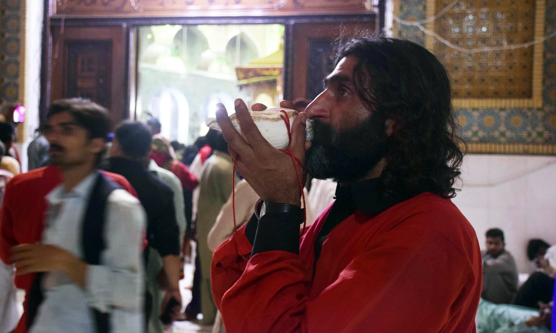 A devotee clad in a red-coloured dress blows on a seashell horn as a mark of his respect for Qalandar.