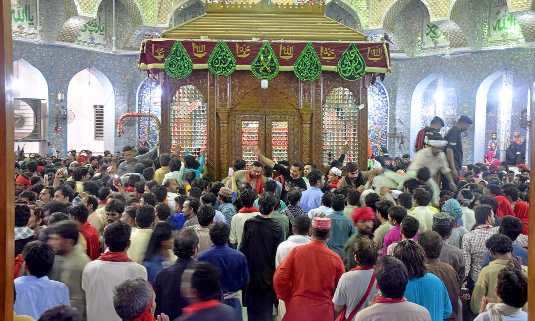 Devotees throng the inner sanctum of Qalandar's shrine at midnight between April 23 and 24.