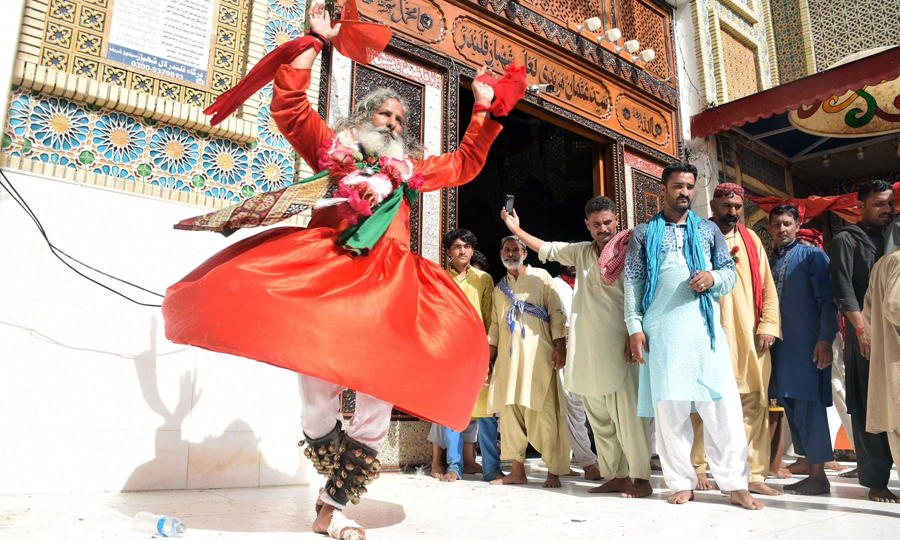 An elderly devotee with a pair of anklets fitted with bells performs a Sufi dance at the main entrance of the shrine.