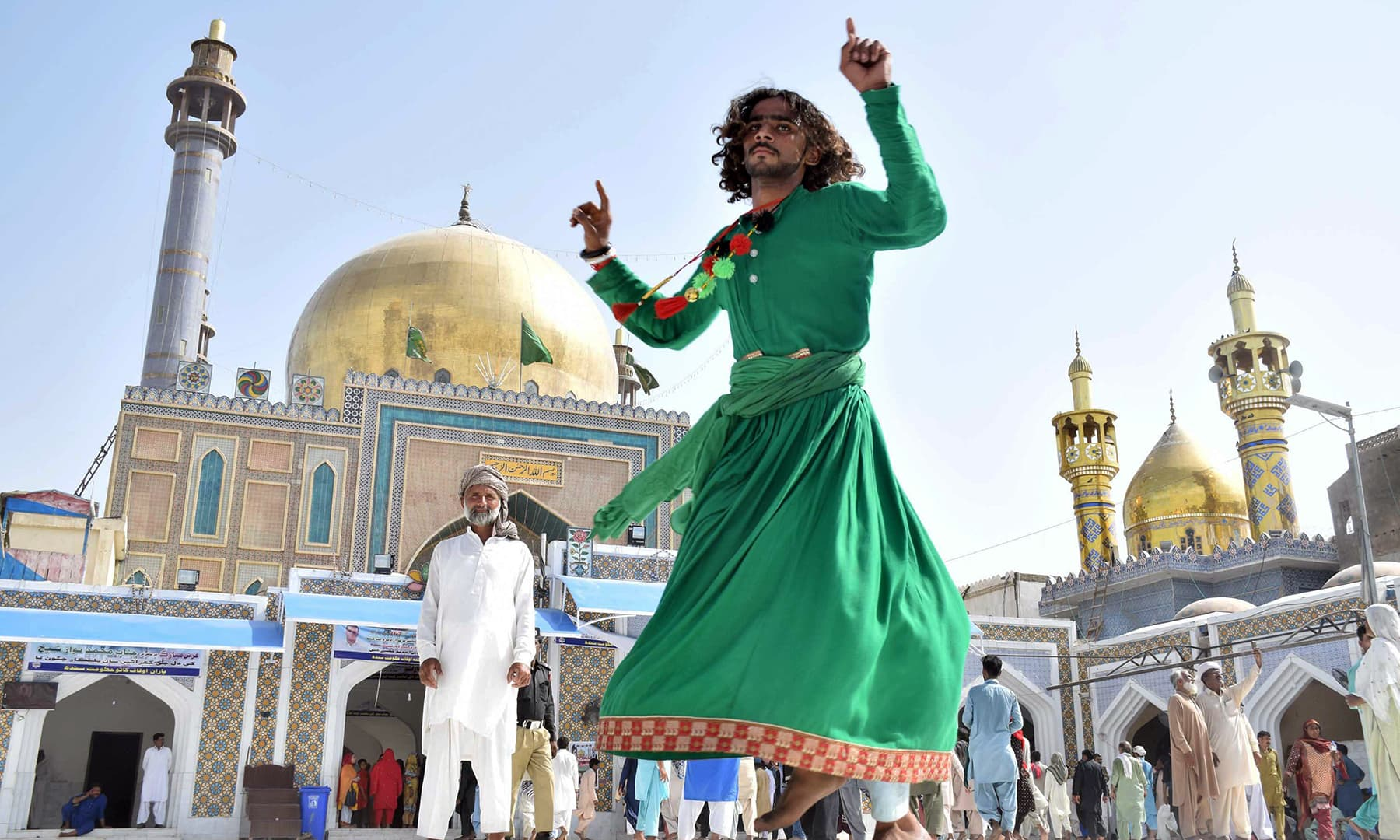 Resplendent in a green frock, a devotee performs a Sufi dance in the shrine's courtyard.