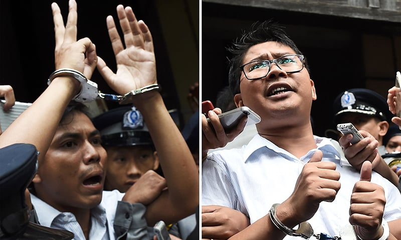 This file combination of photos taken on September 3, 2018 shows journalists Kyaw Soe Oo (L) and Wa Lone being escorted by police after their sentencing by a court to jail in Yangon. — AFP