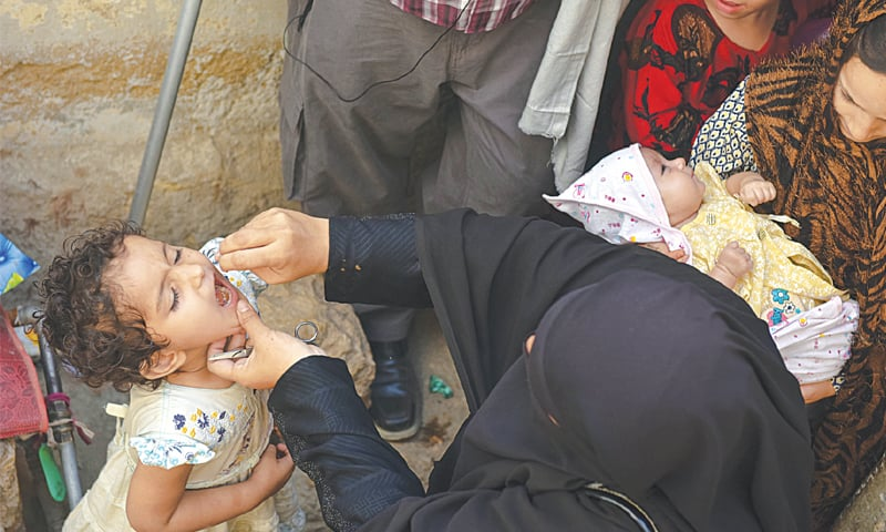 A health worker administering polio drops to a child in Karachi.—Fahim Siddiqi / White Star