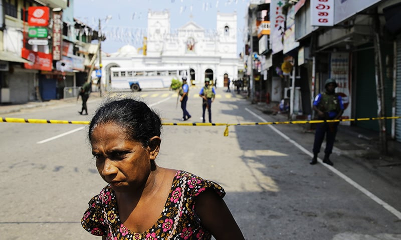 A Sri Lankan ethnic Tamil woman walks on a road leading to St. Anthony's Church. — AP