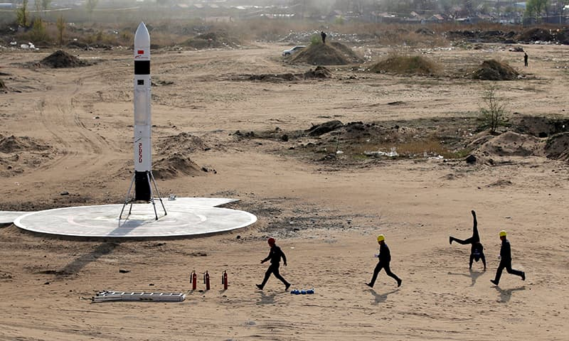 LinkSpace's co-founder and CTO Chu Longfei (2nd R) reacts as he and teammates run close to the reusable rocket RLV-T5, also known as NewLine Baby, after its successful test launch on a vacant plot of land near the company's development site in Longkou, Shandong province, China on April 19, 2019. —Reuters/Jason Lee