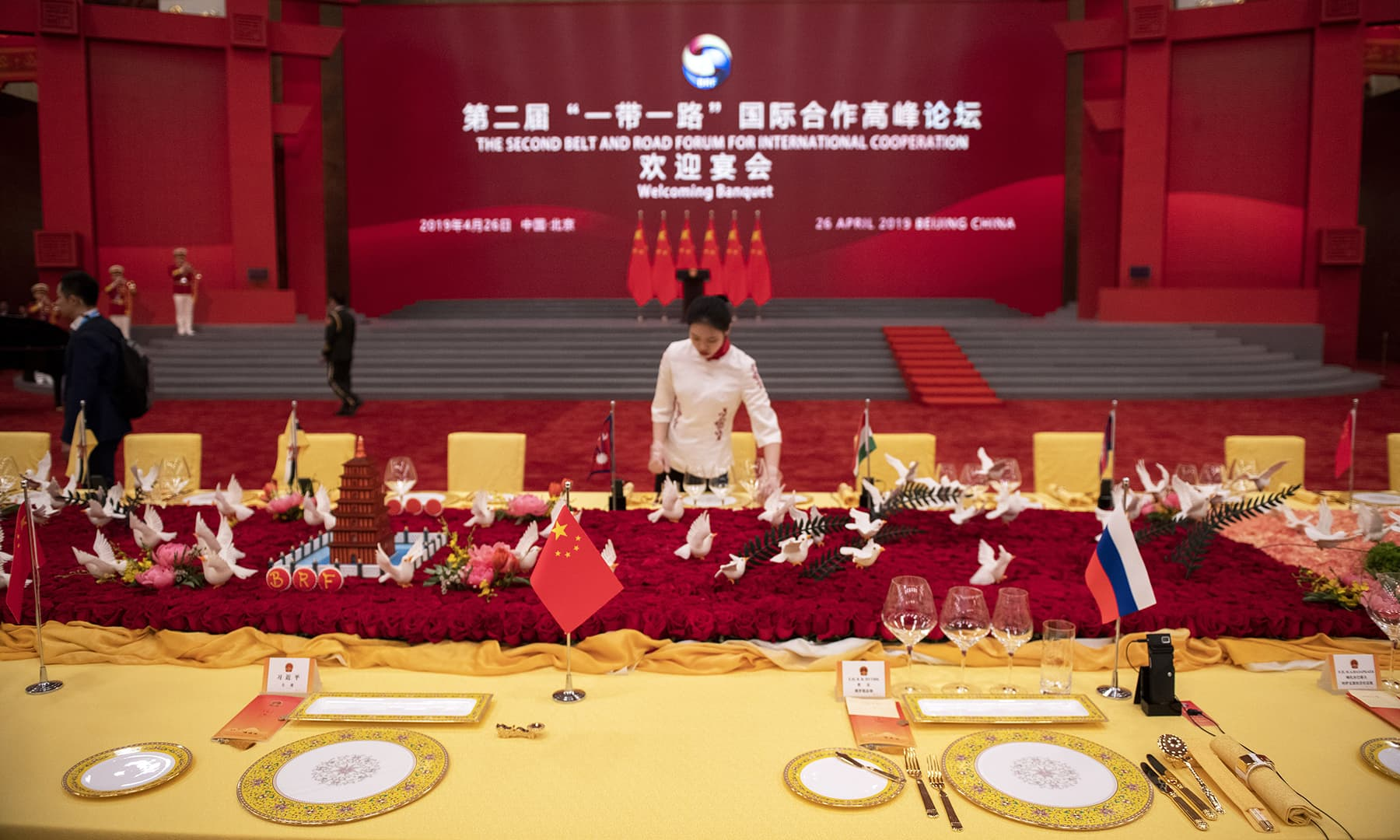 Russian President Vladimir Putin table seat is seen with a full set and Chinese President Xi Jinping table spot, left, is seen without a set yet placed on the table, which are put at the last minute ahead of a welcome banquet for the visiting leaders. — AFP