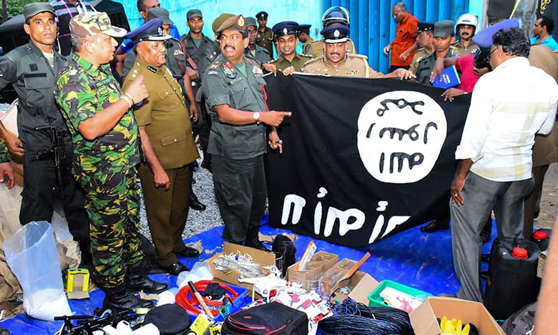 In this picture taken on April 26, security personnel inspect seized items after they raided what is believed to be an Islamist safe house in the eastern town of Kalmunai. — AFP