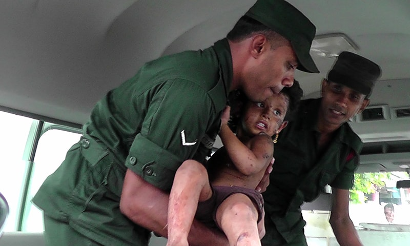 Soldiers evacuate an injured child after the raid in Kalmunai on April 27. — AFP