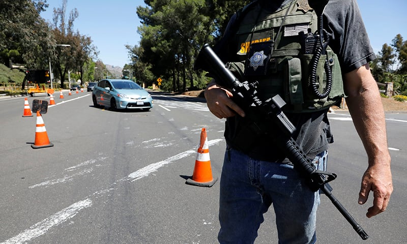 A San Diego County sheriff's deputy secures the scene of a shooting incident at the Congregation Chabad synagogue in Poway, north of San Diego. ─ Reuters