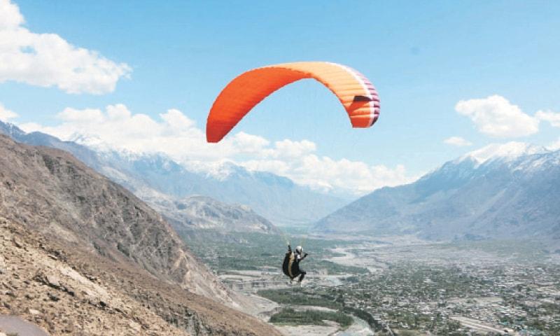 A paraglider flies over Gilgit.—Dawn