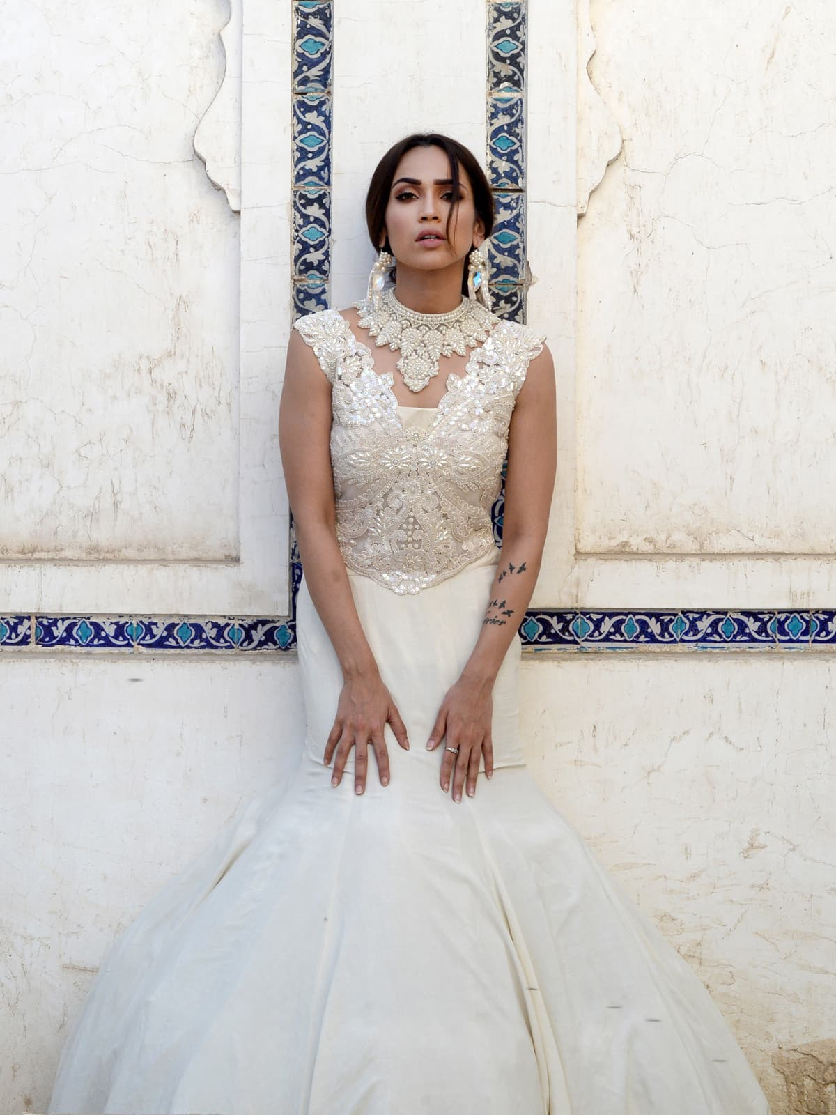 The turquoise blue of the tomb's walls forms the perfect backdrop to the pristine white of Rizwan Beyg's bodice which splays down to a fitted mermaid skirt and is set off by a standout handcrafted neck-piece.