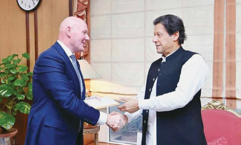 ISLAMABAD: Prime Minister Imran Khan receives a cheque from Guy Meldrum, regional director of the British American Tobacco, for the Diamer-Bhasha and Mohmand Dams Fund at PM Office on Tuesday. — PPI