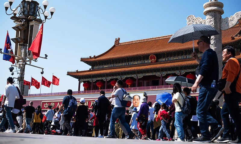 People walk past the Forbidden City near Tiananmen Square to mark May Day, also known as Labour Day, in Beijing. — AFP