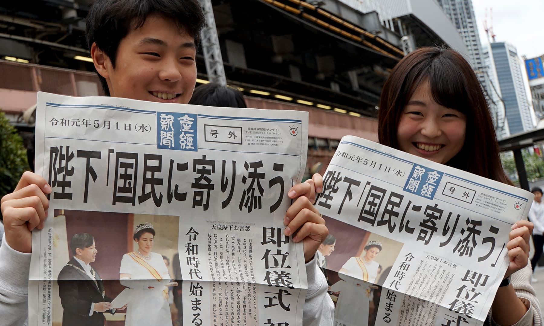 Residents show the extra edition of newspapers reporting new Emperor Naruhito's accession to the throne in Tokyo on May 1, 2019. — AFP