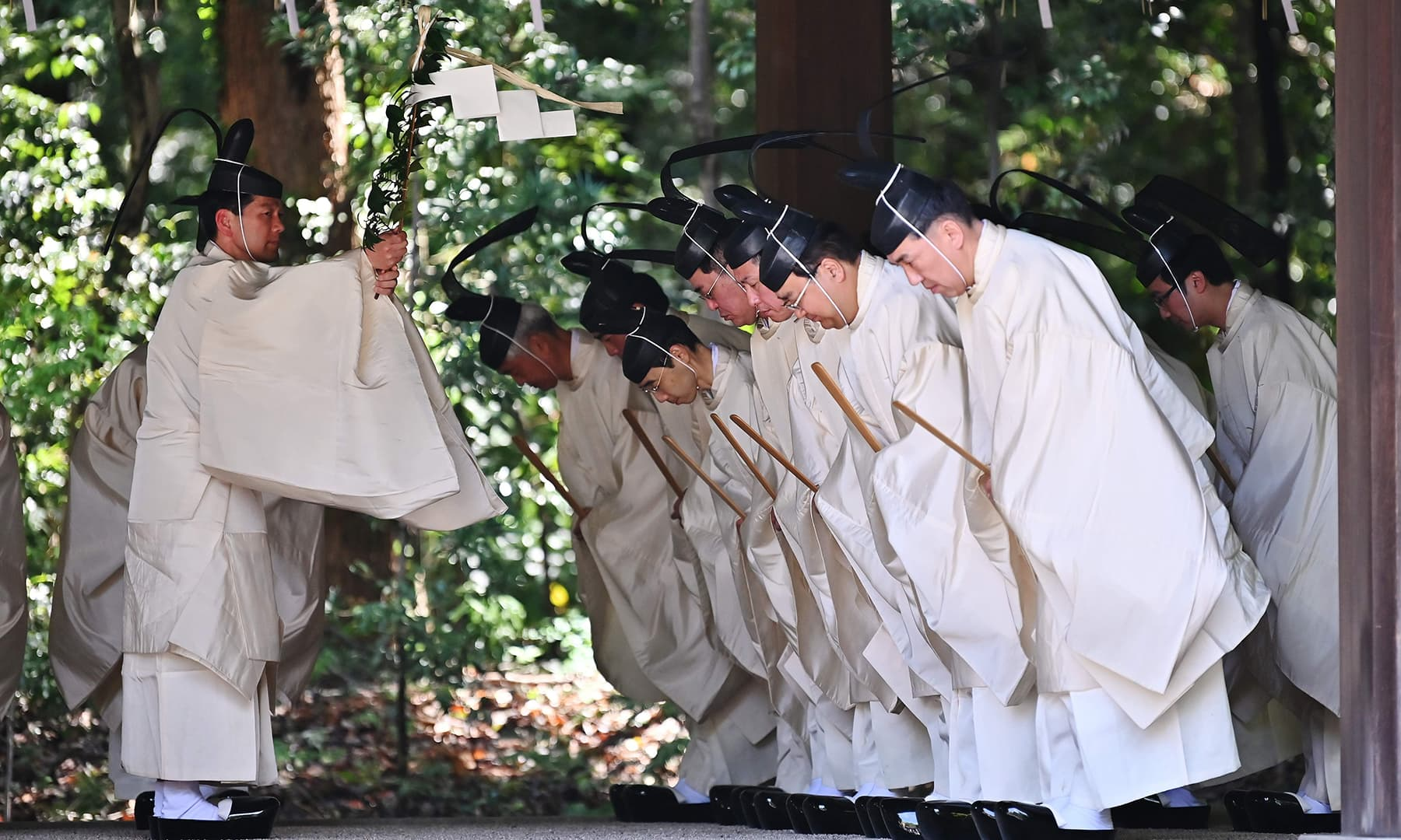Shinto priests recite religious words before entering the main building to conduct a festive ceremony to report the enthronement of the new emperor to the royal family's ancestors at Meiji Shrine in Tokyo. — AFP