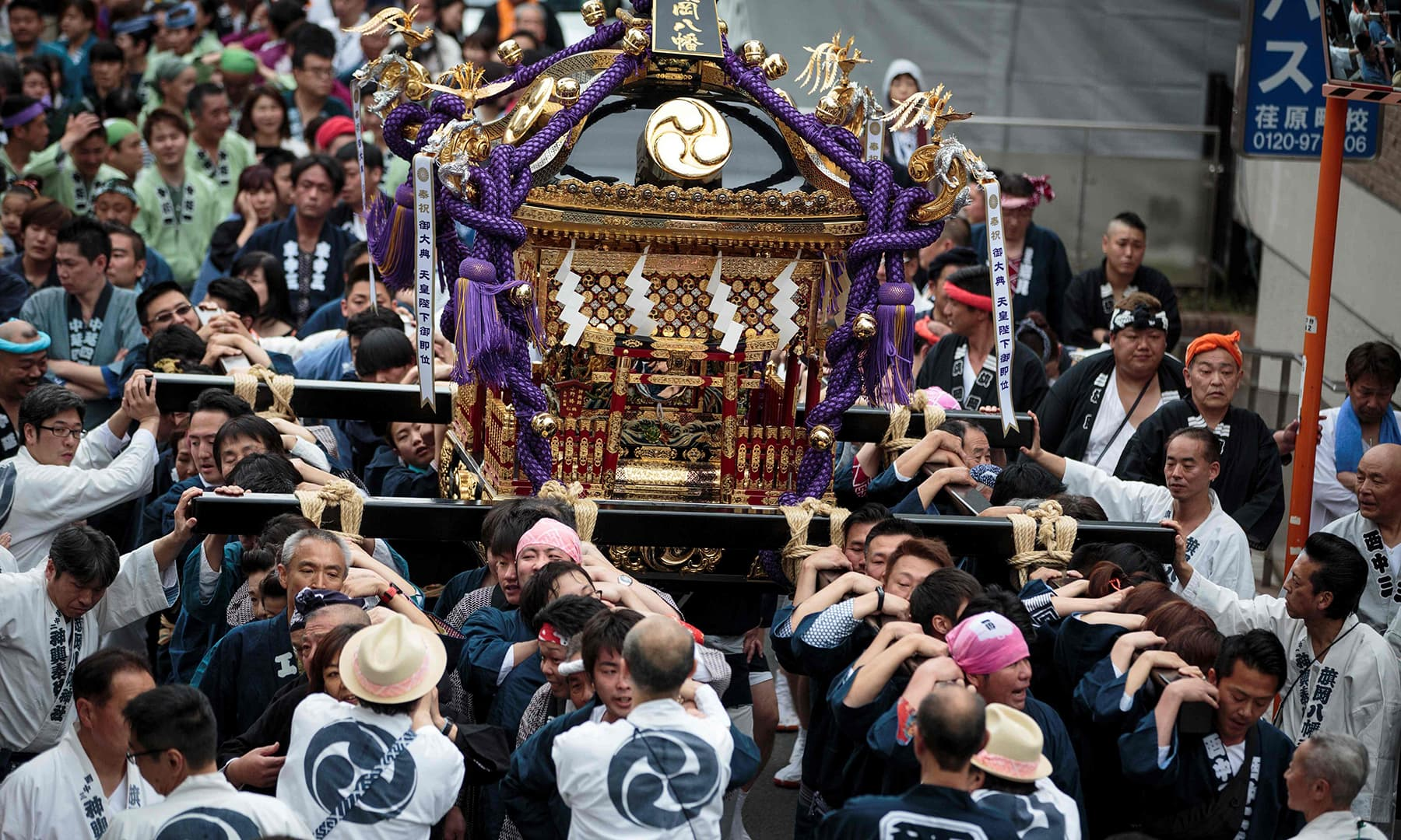"People carry a portable shrine or ""mikoshi"" during a ceremony to celebrate the accession of the new emperor to the throne in the Nakanobu neighbourood of Tokyo. — AFP"
