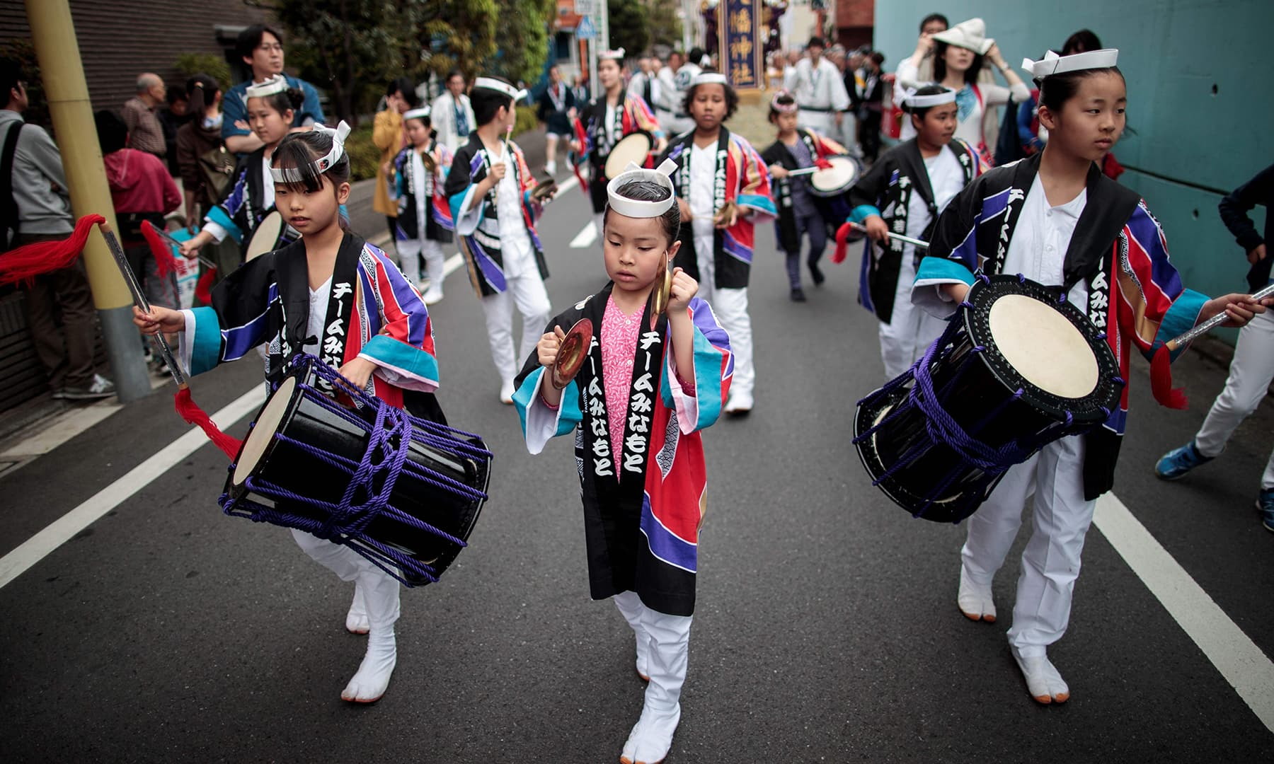 Children play drums during a ceremony to celebrate the accession of the new emperor to the throne in the Nakanobu neighbourood of Tokyo on May 1, 2019. — AFP