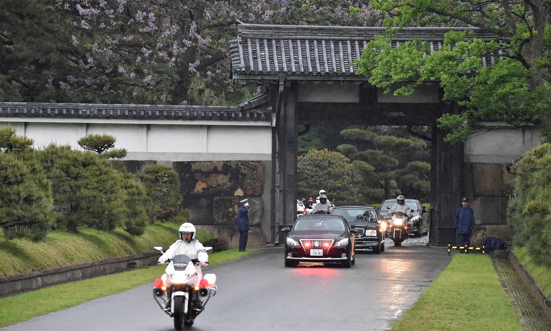 A motorcade transporting Japan's new Emperor Naruhito and Empress Masako leaves through one of the gates of the Imperial Palace in Tokyo. — AFP
