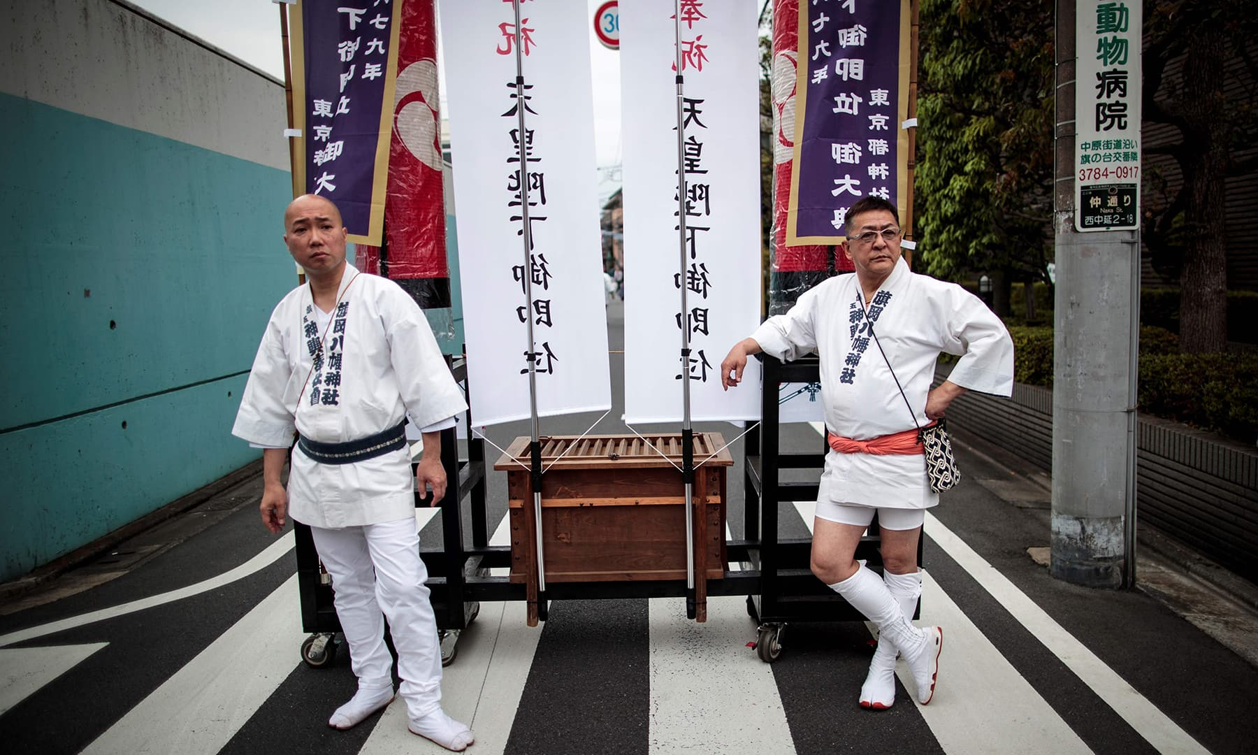"Participants wearing traditional ""hanten"" stand next to the banners during a ceremony to celebrate the accession of the new emperor to the throne in the Nakanobu neighbourood of Tokyo. — AFP"