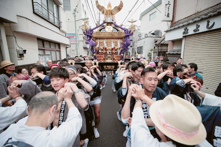 "Tokyo: People carry a portable shrine, or ""mikoshi"", during a ceremony to celebrate the accession in Nakanobu neighbourood.—AFP"