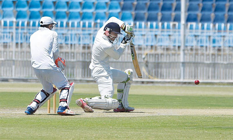 RAWALPINDI: HEC's top-scorer Mohammad Faiq plays a defensive shot as SBP wicket-keeper Rohail Nazir looks on during the Patron's Trophy Grade-II final at the Pindi Cricket Stadium on Friday.