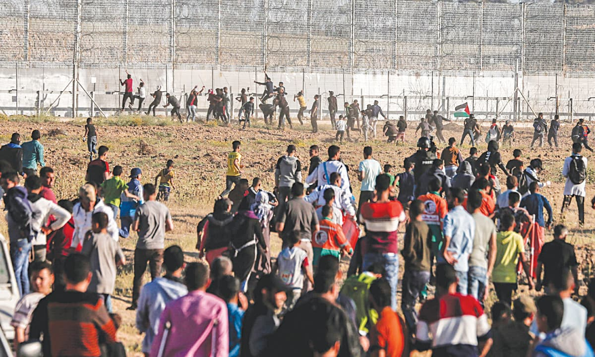 Palestinian protesters try to climb the border fence with Israel during clashes following a demonstration along the border east of Gaza City on Friday.— AFP